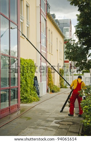 A window cleaner when cleaning an office building - stock photo