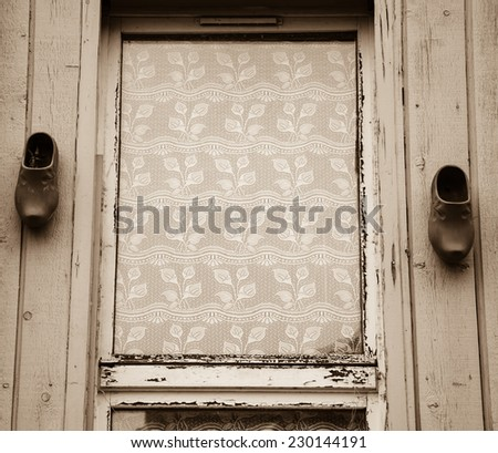A window decorated with lace curtain (leaf pattern) and traditional dutch wooden shoes hanging at weathered plank wall. (Amiens, Picardy, France)  Rustic background. Aged photo. Sepia. - stock photo