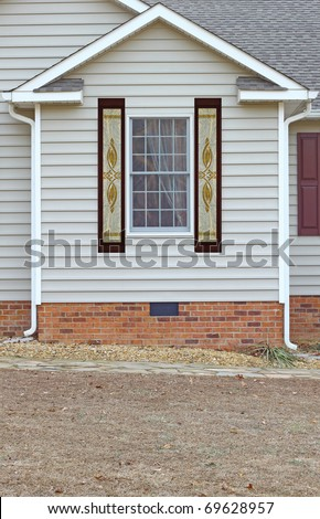 A window in a vinyl sided house with a curtain in it on a brick foundation along with etched glass side windows on both sides with room for your text.