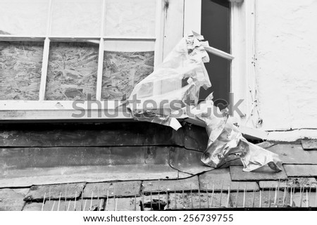 A window in an old house boarded up in black and white - stock photo