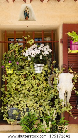 A window of old typical Mediterranean house (with ocher stucco wall and wooden shutters) decorated with flowers, figurine of Madonna with Child Jesus and goat skull with horns. (Cassis, France). - stock photo