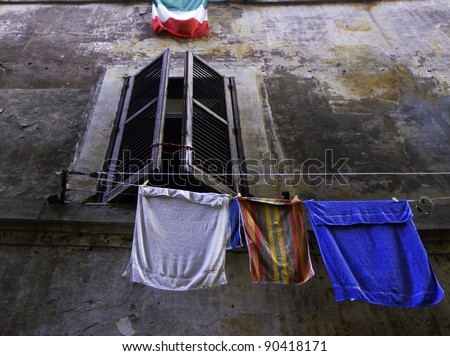 A window, some clothes, the Italian flag and the facade of a building in Rome, Italy
