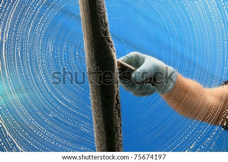 a window washer soaps and cleans a window with a squeegee with room for your text - stock photo