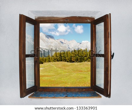 A window with a dark wood frame. The window is open. Ridge of mountains, forest and meadow visible through the open window