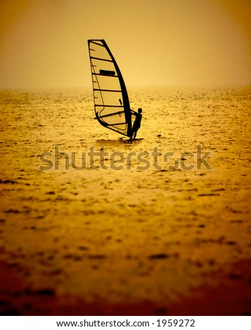 A windsurfer leans back into the breeze  Shot with orange filter.