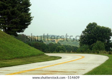 A windy road with a beautiful view. - stock photo