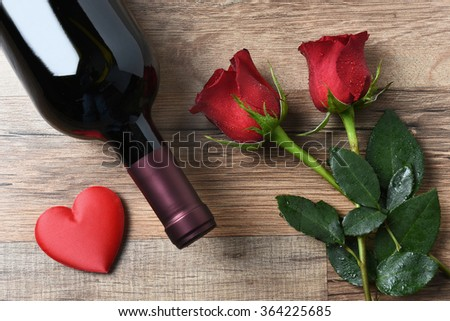 A wine bottle and two red roses and heart on a rustic wood table. Overhead view in horizontal format. Valentines Day Concept. - stock photo