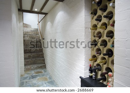A wine cellar with white walls and wine rack