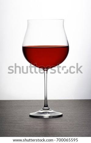 A wine glass(Grand Cru glass on a wooden table in front of a white background. Filled with a red wine