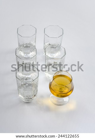 A wine glass with wine while others are empty water glass. Standout concept for those who lead. - stock photo
