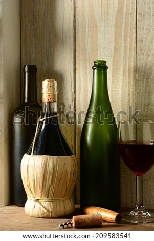 A wine still life with warm light from a window on the side. Three bottles, a wine glass and cork screw in a rustic setting, Vertical format,  - stock photo