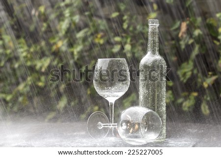 A winebottle and two glasses on a garden table during heavy summer rain - stock photo