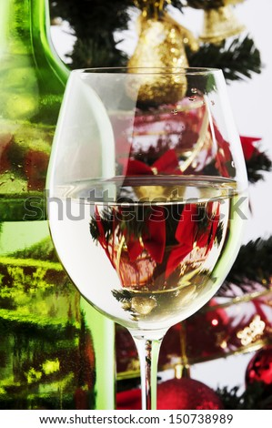 a wineglass and green bottle white wine and Christmas tree and decoration for background  - stock photo