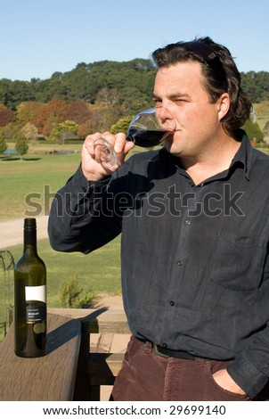 A winemaker sampling the finished product - stock photo