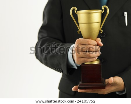 a winner with suit holding a trophy - stock photo