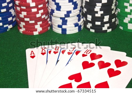 a winning poker hand of a royal flush with stacks of poker chips