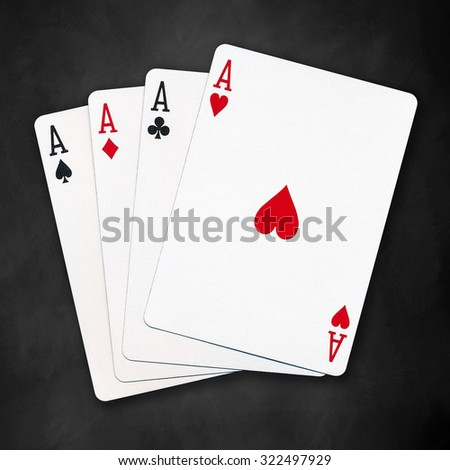 A winning poker hand of four aces playing cards suits on black background - stock photo