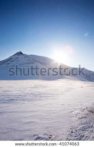 A winter landscape with a mountain and blue sky