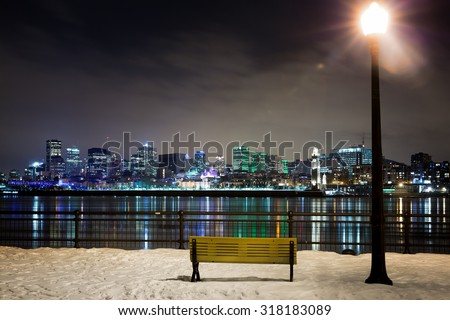 A winter night in Montreal. Park bench and street light with the St Lawrence river and downtown Montreal in the background.