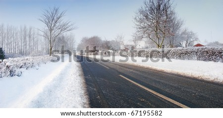 A winter photo of snowy countryside and road - stock photo