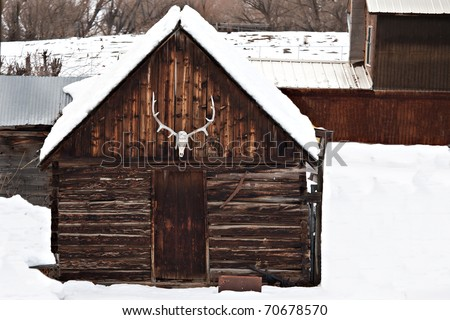 A winter scene in the western US with old an barn, elk antlers, and other farm buildings/ - stock photo