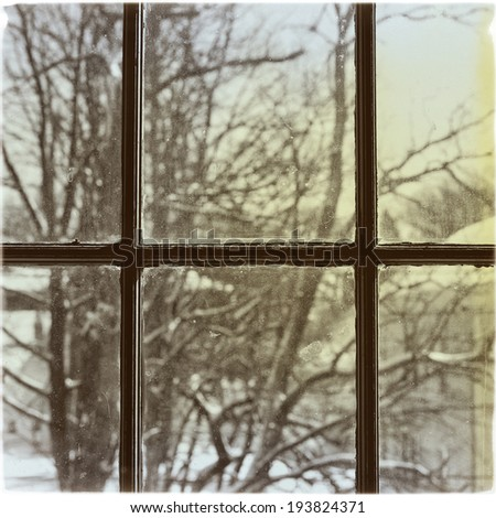 A winter scene of trees through a dirty window, instagram filter style - stock photo