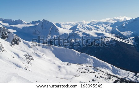 A winter scenic landscape and skiers making the most of a beautiful winter day on the ski run on Blackcomb mountain  - stock photo