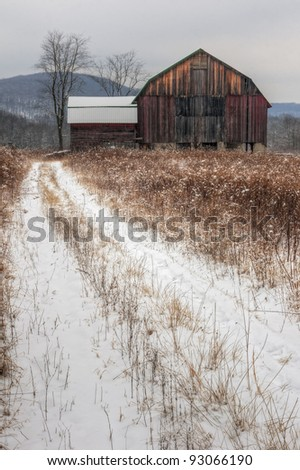 A winter snow scene of a rustic old barn. - stock photo