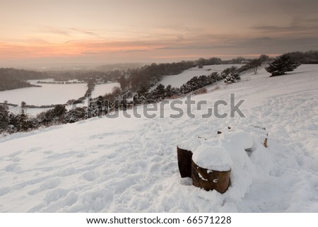 A winter view from the top of Pewley Down in Guildford, Surrey, UK.  The landscape is covered in snow.  Taken just after sunset in December. - stock photo