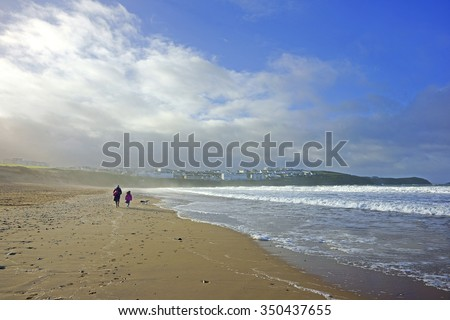 A winter walk along Fistral Beach with an incoming tide and a clearing sea mist in the distance, near Newquay, Cornwall, South West England, United Kingdom - stock photo