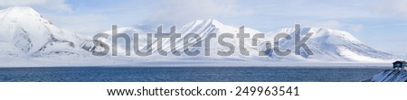 A winter wilderness - mountainous landscape along sea coast on the island of Spitsbergen, Svalbard, Norway  - stock photo
