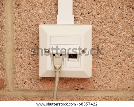 A wire in an ethernet socket for two devices on a building wall - stock photo
