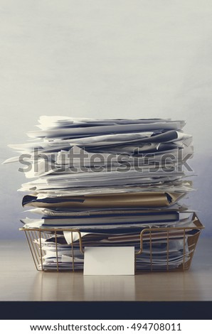 A wire office tray with blank label, piled up with papers and folders, undersaturated in drab hues for dreary, dystopian feel.