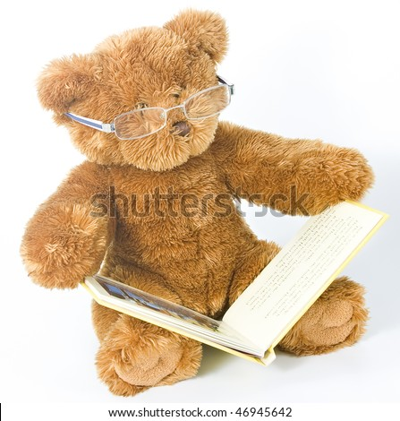A wise old teddy bear looking at a book with the aid of his reading glasses
