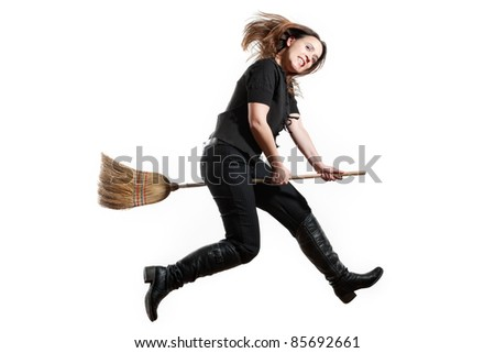 A witch flying through the air grinning like a maniac on white - stock photo