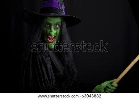 A witch riding on a broomstick. - stock photo