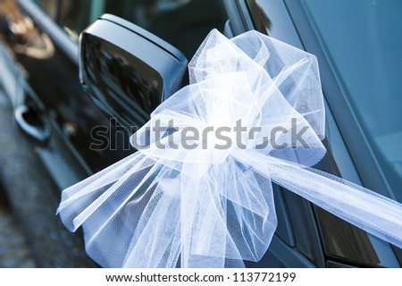 a withe ribbon on a wedding car