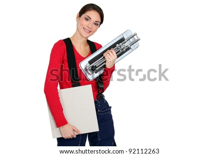 A woman about to lay tiles/ - stock photo