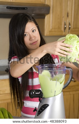 A woman adding a little lettuce into her blender to add a little fiber to her healthy smoothie. - stock photo