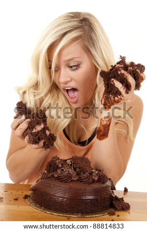 a woman after digging into a chocolate cake getting ready to take a bite. - stock photo