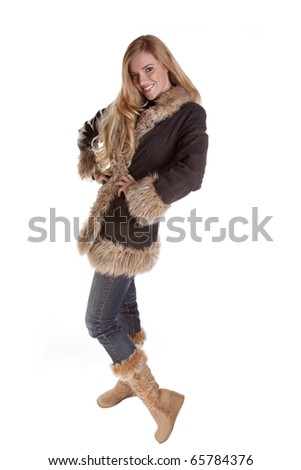 a woman all dressed up in her fuzzy coat and fuzzy boots. - stock photo