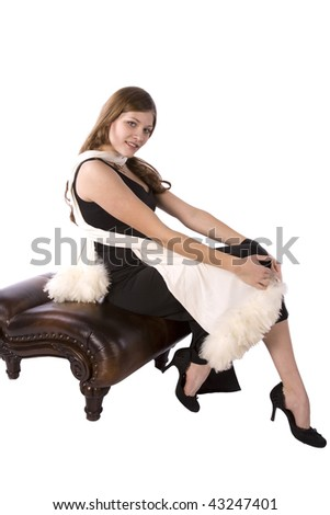A woman all dressed up with a serious expression sitting on a brown bench with her black formal on and fuzzy white scarf. - stock photo