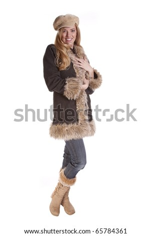 a woman all warm while she is wearing her fuzzy coat and boots. - stock photo