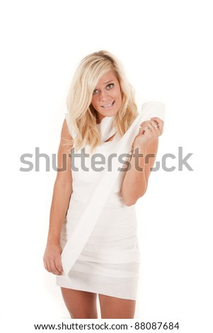 A woman all wrapped up in toilet paper holding the roll with a small smile on her face.