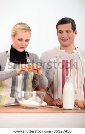 a woman and a boy making a cake - stock photo
