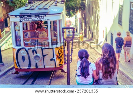 A Woman and a Child waiting for the arrival of the tramway in Lisbon - stock photo
