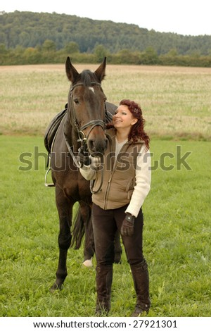 A woman and a horse standing on a background of a field and a hill. - stock photo