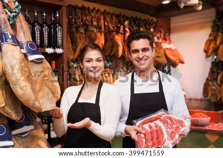 A woman and a man in the shop offer jamon
