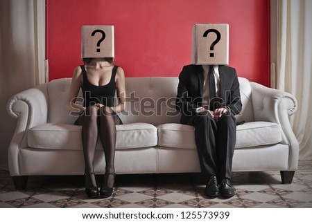A woman and a man sitting on a sofa with a box on which is drawn a question mark over their heads - stock photo