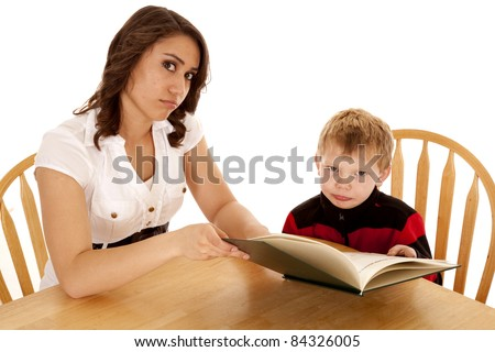 A woman and boy sitting at a table reading a story with a sad expression on their faces.